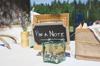 chalkboard sign saying pin a note for bride and groom's guest book