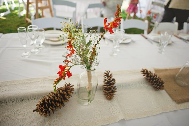 Rustic wedding reception decor with pine cones, burlap, lace and wild flowers