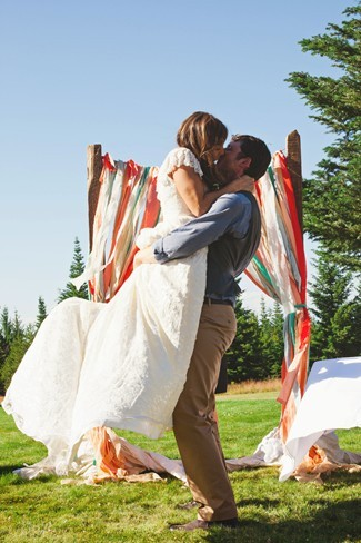 Groom picking bride up during wedding ceremony to kiss her.