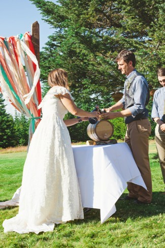 Outdoor wedding ceremony with bride and groom boring beer into barrell