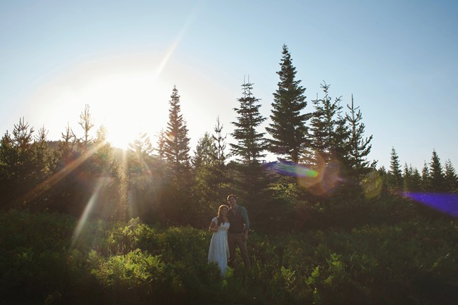 Bride and groom standing on grassy hill with tree behind and the sun shinning throughj