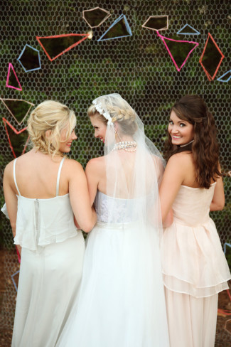 bride standing with bridesmaids in front of colorful octagonal shapes in mesh for wedding backdrop