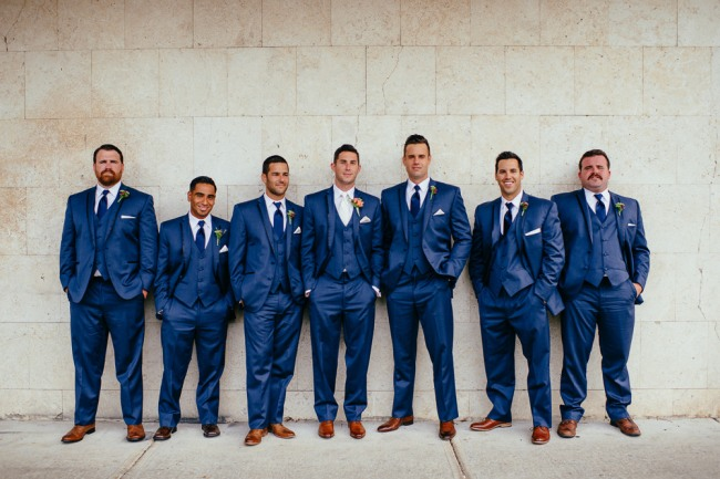 Groom with groomsmen standing with hands in their pockets wearing blue suits