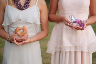 bridesmaids standing in light color dresses holding a donut and a horse figurine