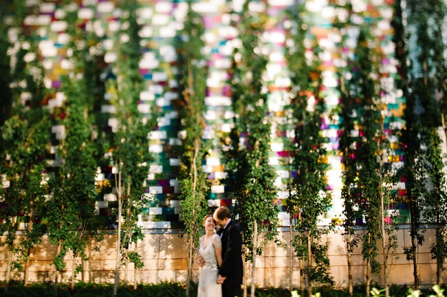 Bride and groom standing in front of multi color wall and hedges in downtown Seattle