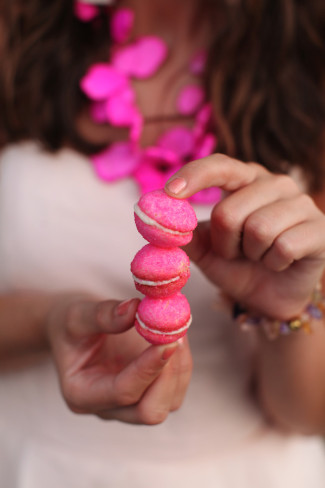 girl holding 3 pink macaroons stacked on top of each other