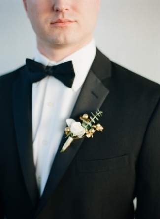 Groom wearing black tux and bow tie with a gold, white and green boutonniere