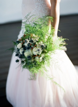 Bride wearing a gown by grace bridal atelier holding a thistle bouquet by Bushel & Peck