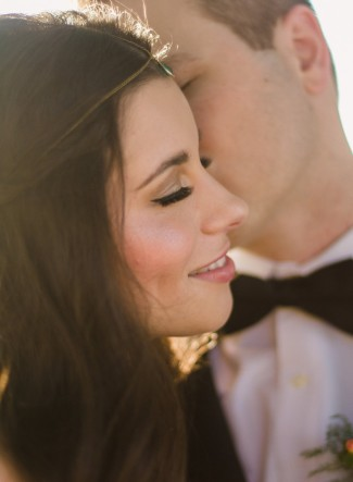 Bride with eyes closed leaning up to grooms mouth