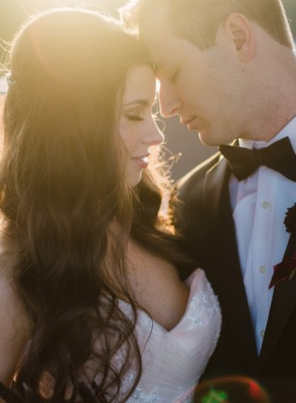 Bride with long flowing curls head to head with groom wearing black tux