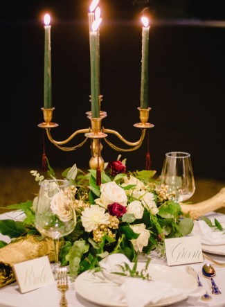 Gold candelabra with green candles and floral center piece by Bushel & Peck