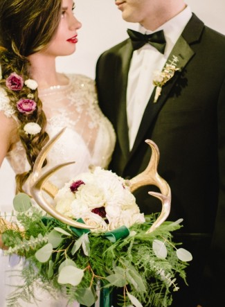 Bride with a braid carrying a white bouquet with green foliage and gold antlers