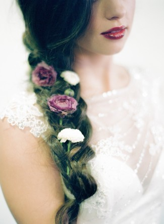 Bride with long brown hair braided with large white and purple flowers weaved within the braid