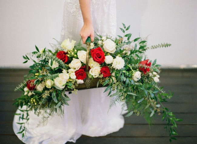 bride carrying a bronze basket full of loose bouquet of red and white roses and olive branches