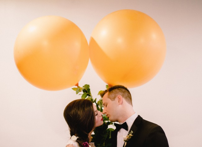 Bride and groom about to kiss under blush colored geronimo balloons