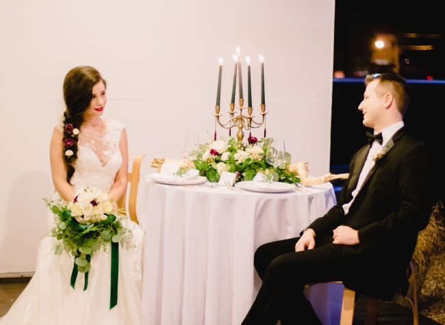 Bride and groom sitting at table with a gold candelabra with green candles and floral centerpiece