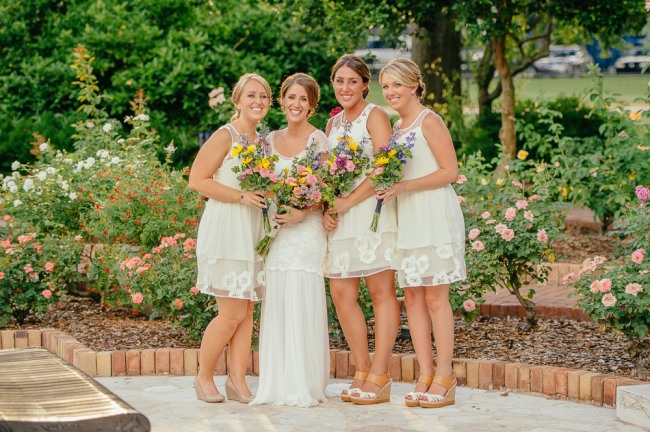 bride with bridemaids wearing white dresses and carrying wild flower bouquets