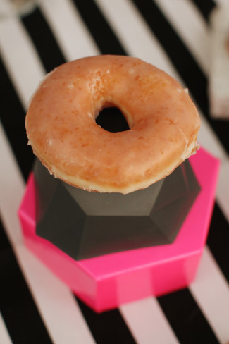 glazed donut stacked on top of gray and pink octagon shapes