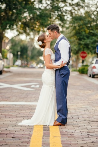 bride and groom kissing in the middle of a street
