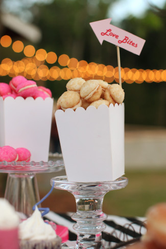 "white and pink macaroons in a popcorn caddy with a sign saying ""love bites"""