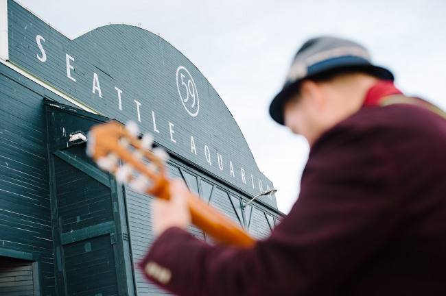 Man playing guitar with Seattle Aquarium sign behind him