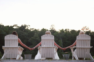 bride with bridemaids sitting in white wood loungers and holding hands