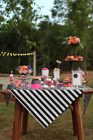 colorful dessert table with donuts, black and white stripped table cloth and pink accents
