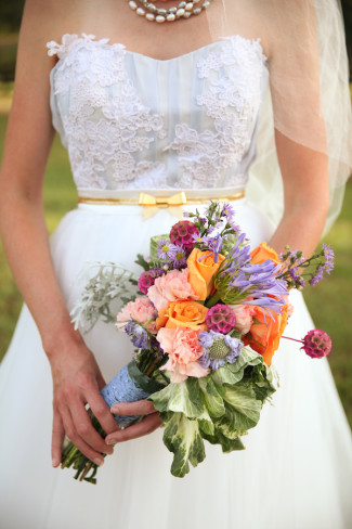 bride wearing strapless gown with gold belt holds flowers