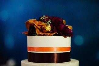 white wedding cake with dark down and orange ribbon and floral topping