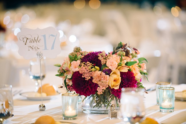 Wedding reception table with white table cloth and pink, purple and peach flowers and a blue table number