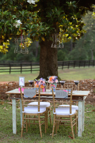 outdoor wedding reception table with gold chairs and pink accents