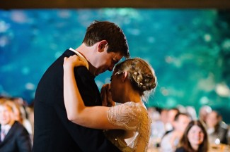 Bride and groom's first dance in front of fish tank at wedding reception at Seattle aquarium