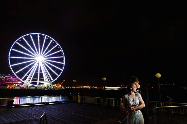 Bride and groom standing on downtown Seattle Pier with Ferris wheel in the background lite up