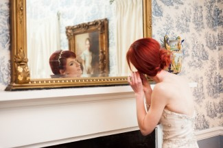 bride putting on earring in front of large mirror