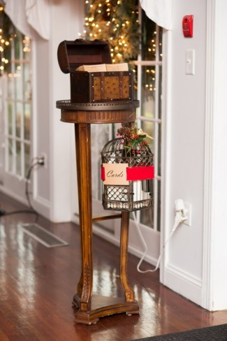 vintage small stand holds chest on top and hanging birdcage for cards