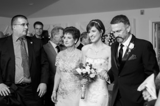 black and white photo of bride and her parents walking down aisle