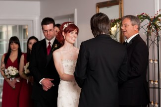 bride and groom holding hands at alter for indoor ceremony at Antrim 1844 Hotel