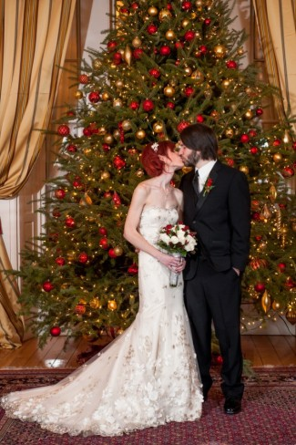 bride and groom kiss in front of giant decorated Christmas tree