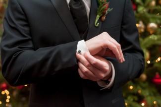 groomsman in black necktie adjusting cufflink