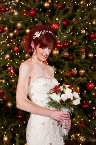 Bride holding bouquet with giant Christmas tree in background