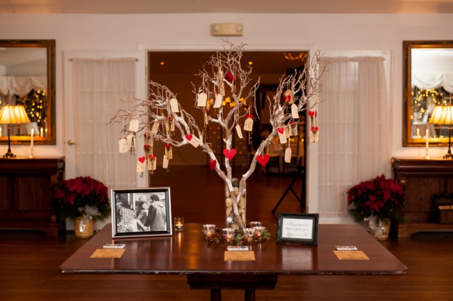 Tree branches in vase on table with table number tags hanging
