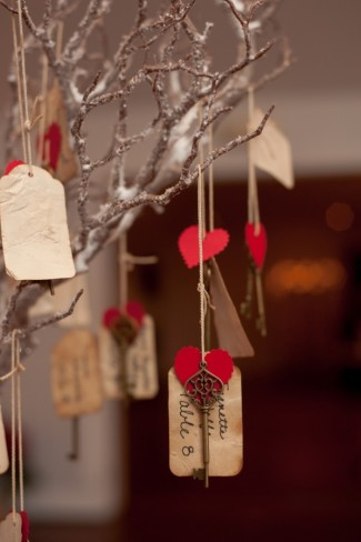 Closeup of table number tag hanging from branch with vintage key