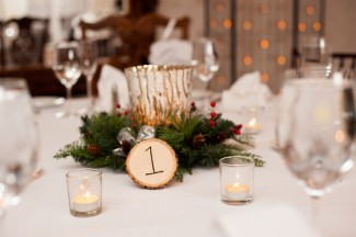 Holly berry, boughs, and wood slice table number centerpiece