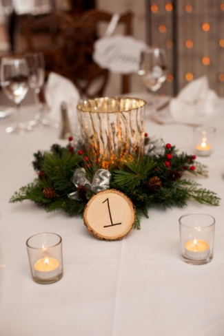 candle, holly berries, pine cone, and wood slice centerpiece