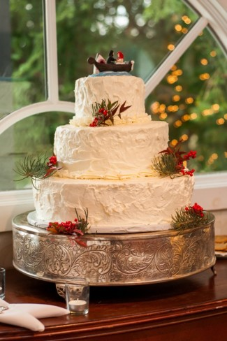 3-tier wedding cake with fir tree and holly berries on silver cake stand