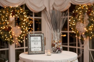 sparklers in vase on table with wreaths and white lights behind