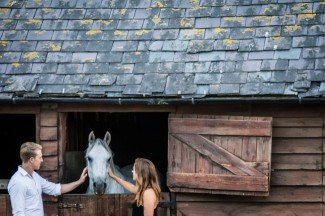Couple pet horse in barn stall