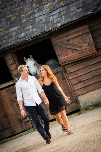 Couple walk next to horse barn stall