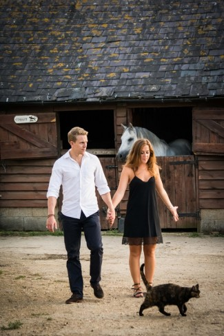 Couple walk next to horse barn stall with black cat running
