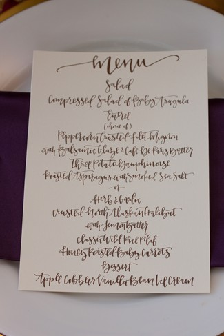 white dinner party plate with purple napkin and menu card on top